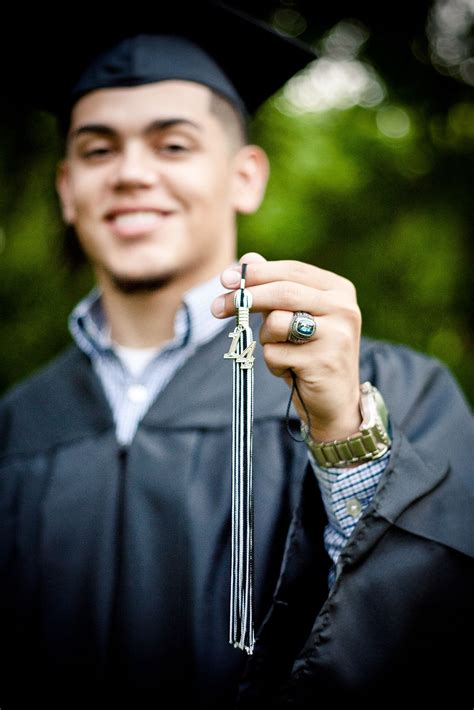 Senior portrait with cap and gown and showcasing his
